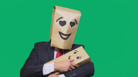 concept of emotions, gestures. a man with a package on his head, with a painted emoticon, smile, enamored eyes. plays with the child painted on the box Stock Photo