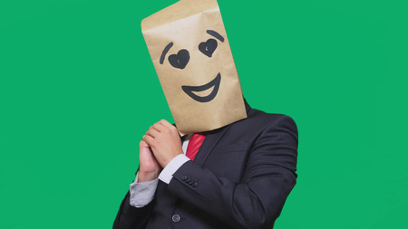 concept of emotions, gestures. a man with paper bags on his head, with a painted emoticon, smile, joy, love eyes