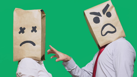 The concept of emotions and gestures. Two people in paper bags with smileys. Aggressive smiley swears. The second listens to him wearily.