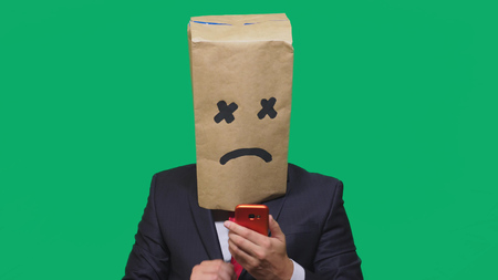 concept of emotion, gestures. a man with a package on his head, with a painted smiley, exhausted, tired, talking on the phone.