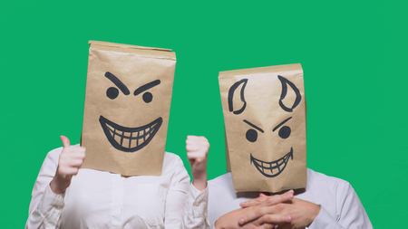 concept of emotions, gestures. a man with a package on his head, with a painted emoticon, sly and the devil laugh. trolling , lie, provocation. Banque d'images