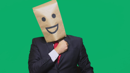concept of emotions, gestures. a man with paper bags on his head, with a painted emoticon, smile, joy. 版權商用圖片