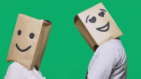 concept of emotions, gestures. a couple of people with paper bags on their heads, with a painted emoticon, smile, joy, eyes in love