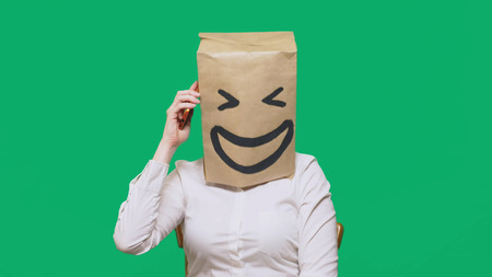 concept of emotions, gestures. a man with paper bags on his head, with a painted emoticon, smile, joy. talking on a cell phone. Stock Photo