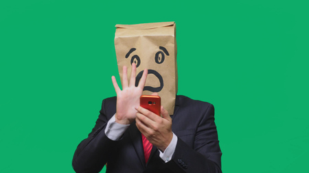 concept of emotions, gestures. a man with paper bags on his head, with a painted emoticon, fear. talking on a cell phone. 免版税图像