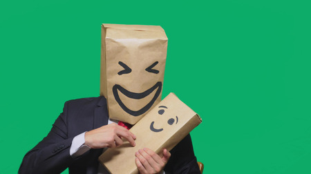concept of emotions, gestures. man with a package on his head, with a painted emoticon, smile, joy, laughter. plays with the child painted on the box Stock Photo