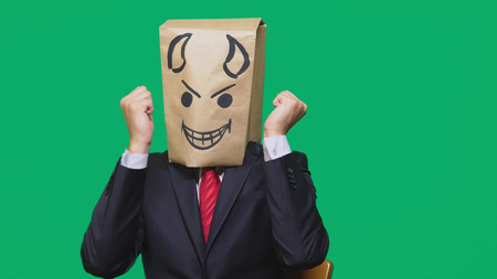 concept of emotion, gestures. a man with a package on his head, with a painted smiley angry, sly, gloating, devil. Stock Photo