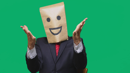 concept of emotions, gestures. a man with paper bags on his head, with a painted emoticon, smile, joy. Stock Photo