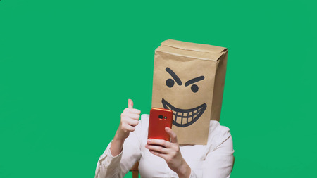 concept of emotions, gestures. a man with a package on his head, with a painted black emoticon, crafty, gloating, talking on a mobile phone