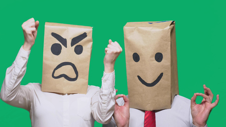 The concept of emotions and gestures. Two people in paper bags on the head with painted smileys. Aggressive smiley swears. The second smiles at him