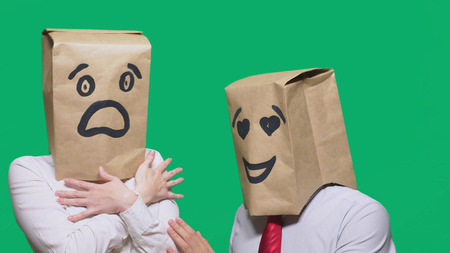 concept of emotions, gestures. a couple of people with bags on their heads, with a painted emoticon, a smile, eyes in love, and the second with a mask of fright, fear. sexual harassment concept.