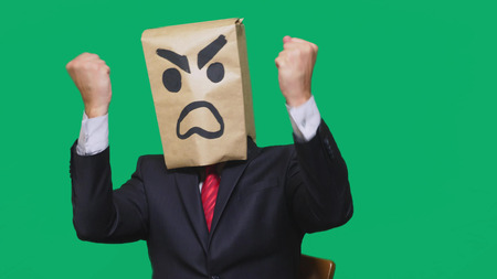 concept of emotion, gestures. a man with a package on his head, with a painted smiley aggressive, angry 版權商用圖片