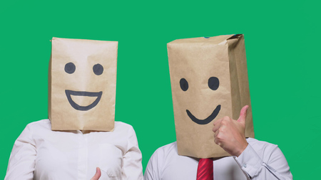 concept of emotions, gestures. a couple of people with bags on their heads, with a painted emoticon, smile, joy, laugh Stock Photo