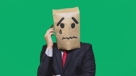concept of emotion, gestures. a man with a package on his head, with a painted smiley crying, sad, talking on the phone. Banque d'images