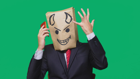 concept of emotions, gestures. a man with a package on his head, with a painted black smiley face, a devil, crafty, gloating, talking on a mobile phone