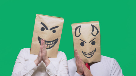concept of emotions, gestures. a man with a package on his head, with a painted emoticon, sly and the devil laugh. trolling , lie, provocation. Stockfoto