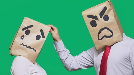 Le concept des émotions et des gestes. Deux personnes dans des sacs en papier avec des smileys. Un smiley agressif jure. Le second pleurait triste.