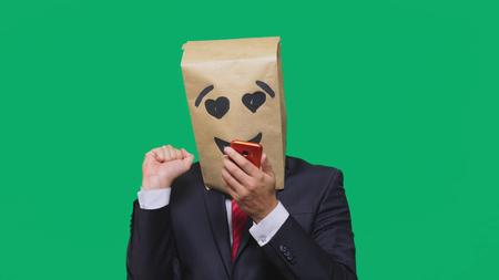 concept of emotions, gestures. a man with paper bags on his head, with a painted emoticon, smile, joy, love. talking on a cell phone.
