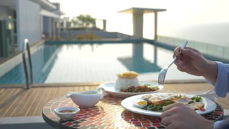 Shrimp soup is a Thai dish with a sour and spicy taste. the man is eating Tom Yam at a table by the pool. close-up. concept of tourism tourism.