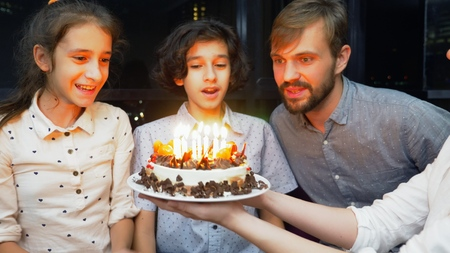 Happy smiling boy blowing candles on her birthday cake. children surrounded by their family. birthday cake with candles Stockfoto
