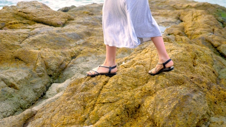 close-up. womens legs in sandals and a long gray skirt are on the rocky seashore at low tide