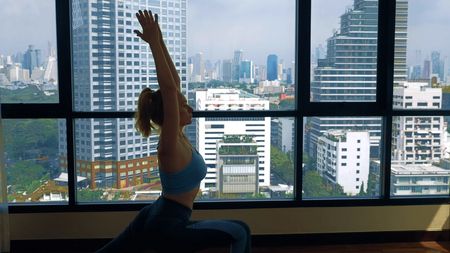 young woman doing yoga in a room near a large window overlooking the skyscrapers.