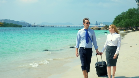 businessman and business woman with a suitcase walking along the white sand beach on the island