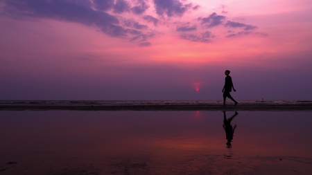 silhouette. lonely asian young man walking peacefully along a deserted beach at sunset. seascape Stockfoto - 116129670