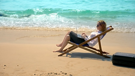 businesswoman working on a laptop while sitting in a lounger by the sea on a white sandy beach. freelance or workaholism concept.
