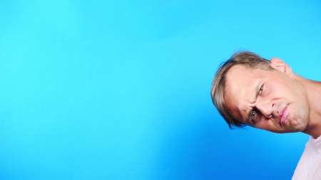 Young man on a colored blue background. portrait. emotions and gestures, close-up. the guy looks in the camera with interest. whats happening .
