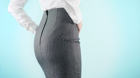 Beautiful business woman on a colored background. close-up skirt. dress code, move the hips.