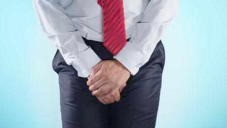 a person has problems with the genitourinary system. businessman on a colored background. close-up Stock fotó