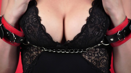 Topless beauty woman body covering her breast. Close-up. A woman with a big chest caresses her breast. handcuffed. bdsm