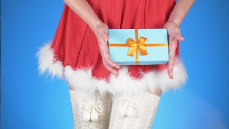 Christmas Holidays. young attractive woman in a snow maiden costume with a gift, dancing on a blue background. close-up