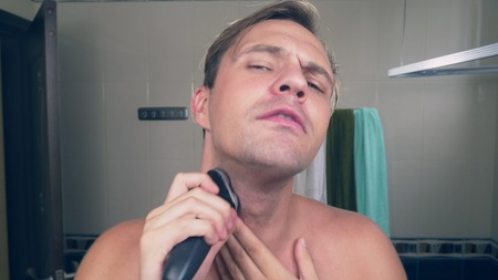 a handsome young man shaves his beard with an electric shaver, standing in the bathroom in front of the mirror.