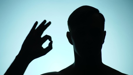 background color. shadow of a person. the guy shows gesture ok