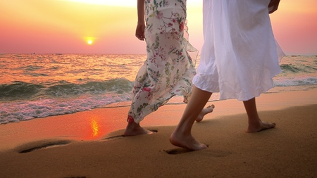 close up . bare feet on the beach. two young women in white dress walking on the beach at sunset