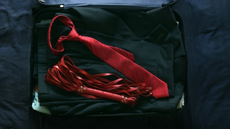The concept of sex tourism. close up, a businessman collects a suitcase and puts a BDSM device in it