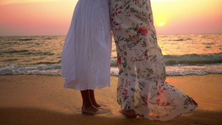 mother and daughter in white dresses walk barefoot on a sandy beach, holding hands against the backdrop of a magnificent sunset
