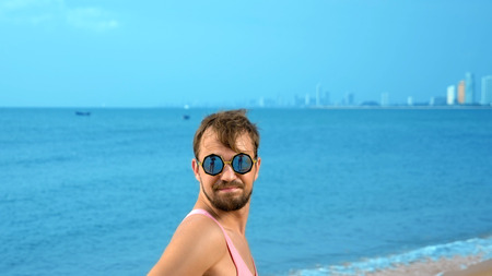Close-up, Playful handsome guy in pink t-shirt on a tropical beach. he looks at the camera, rejoices and makes funny faces Archivio Fotografico