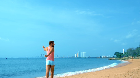 Playful handsome guy in a pink t-shirt and blue shorts rejoices at the beach. freak on the sea. Imagens