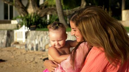 El concepto de las extrañas aventuras de las personas. Pareja feliz con nena caminando en la hermosa playa tropical.