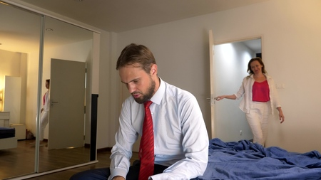tired man sitting on the bed after work day. An attractive charming seductive woman enters the bedroom and whispers pleasant words to her sleepy tired man.
