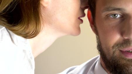 Jolie femme séduisante séduisante chuchotant des mots agréables à son homme fatigué endormi. fermer