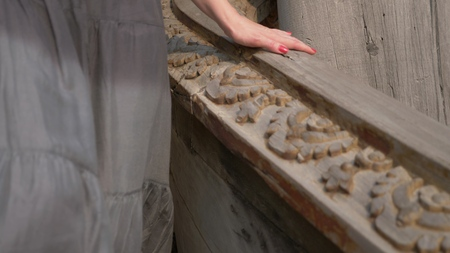 close-up. womans hand slides on a wooden carved railing in a wooden buddhist temple