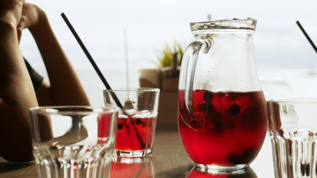 Refreshing red lemonade with berries in a jug on a table in a cafe Imagens - 121413268