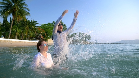 happy couple business woman and businessman in suit and sunglasses splashing into the sea at luxury resorts. The concept of a long-awaited vacation, freelancing.