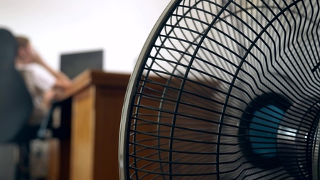 close-up of part of an office fan, on the background of a blurred writing desk, at which a person works at a computer Stock fotó