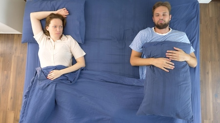 concept of problems in a pair. problems. couple, displeased man and woman are lying in bed. view from above.