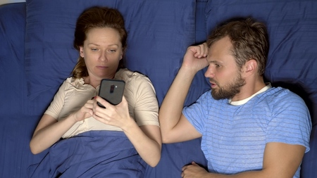 concept of a problem in sex. couple in bed. husband is upset while his wife is using a mobile phone, ignoring him in a relationship Stock Photo